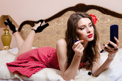 Beautiful pinup girl doing make up in bed Royalty Free Stock Photos