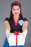 Beautiful pinup girl giving a present Stock Image