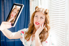 Beautiful pinup girl happy smiling and taking selfie or selfy photo with tablet pc at home by window blinds closeup portrait Stock Image
