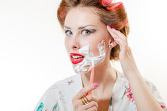 Beautiful pinup girl shaving face looking at camera isolated on white copy space background portrait image Stock Photo