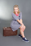 Beautiful pinup girl sitting on brown retro suitcase Stock Photography