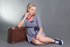 Beautiful pinup girl sitting with brown retro suitcase Stock Images