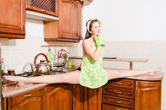 Beautiful pinup woman doing splits in kitchen Stock Images