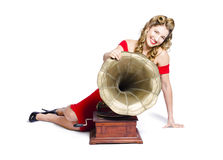 Beautiful pinup woman listening to old gramophone Stock Photo