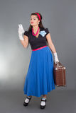 Beautiful pinup woman with retro suitcase and phone Royalty Free Stock Image