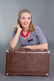 Beautiful pinup woman sitting with brown retro suitcase Royalty Free Stock Photo