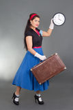Beautiful pinup woman with suitcase and clock Royalty Free Stock Images