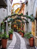 Beautiful places in the magical tiny town in Italy alley. Way with arch flowers Stock Photo