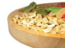 Beautiful plate. Cashew nuts, bay leaves and colored slices of pineapples on wooden plate Royalty Free Stock Photography
