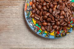 A beautiful plate of coffee beans stands on the old wooden table stock photos