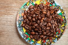 A beautiful plate of coffee beans stands on the old wooden table stock images