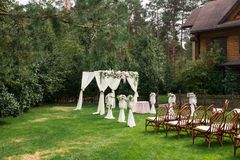 The beautiful platform for a wedding ceremony under the open sky: wooden chairs on a green grass, the square arch decorated with f. Resh flowers. Wedding Stock Images