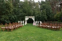 The beautiful platform for a wedding ceremony under the open sky: wooden chairs on a green grass, the square arch decorated with f. Resh flowers. Wedding Stock Photography