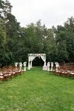 The beautiful platform for a wedding ceremony under the open sky: wooden chairs on a green grass, the square arch decorated with f. Resh flowers. Wedding Royalty Free Stock Photography