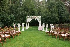 The beautiful platform for a wedding ceremony under the open sky: wooden chairs on a green grass, the square arch decorated with f. Resh flowers. Wedding Royalty Free Stock Photo