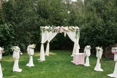 The beautiful platform for a wedding ceremony under the open sky: wooden chairs on a green grass, the square arch decorated with f. Resh flowers. Wedding Stock Photo