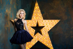 Beautiful playful adult blonde woman wearing dark blue lace tutu. Skirt and mesh stockings posing over dark background with glowing star. Actress playing on Royalty Free Stock Photo