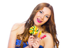 Beautiful playful girl holding colorful twisted lollipops Royalty Free Stock Photo