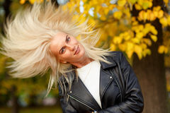 Beautiful playful woman with long blonde hair in autumn park Royalty Free Stock Image