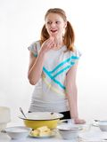 Beautiful pleasant girl prepares baking in kitchen. The beautiful young cheerful girl on home cuisine cooks dough for easter pie Royalty Free Stock Image