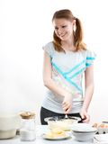 Beautiful pleasant girl prepares baking in kitchen. The beautiful young cheerful girl on home cuisine cooks dough for easter pie Royalty Free Stock Photo