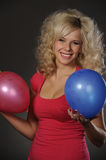 Beautiful plump woman. Playing with balloons on dark background Stock Photos