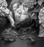 Beautiful plus size model lying in flowers. Black and white. Young beautiful plus size model lying in flowers, xxl woman portrait, professional makeup and Stock Photos