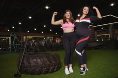 Beautiful plus size sportswomen exercising at the gym together. Two happy confident plus size women smiling, flexing their biceps at the gym, copy space. Happy stock photography