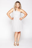 Beautiful plus size woman. Full-length portrait of beautiful plus size curly young blond woman posing on gray in white dress and court shoes stock image