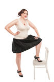 Beautiful plus size woman with chair Royalty Free Stock Photography