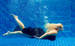 Beautiful plus size woman diving in pool. Beautiful young plus size woman diving in pool royalty free stock image