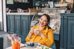 Beautiful plus size woman eating dessert in cafe stock images