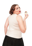 Beautiful plus size woman eating pastry. Isolated Royalty Free Stock Photo