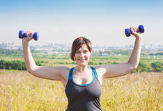 Beautiful plus size woman exercising with dumbbells Royalty Free Stock Image