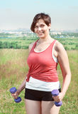 Beautiful plus size woman exercising with dumbbells. Outdoor Royalty Free Stock Images