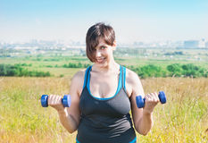 Beautiful plus size woman exercising with dumbbells Stock Image