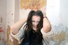 Beautiful plus size woman expresses delight. Against an old wall stock image