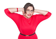 Beautiful plus size woman in glasses covering her ears with her Stock Image