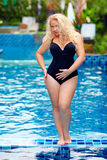 Beautiful plus size woman posing in the pool. Beautiful young plus size woman posing in the pool royalty free stock image