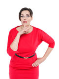 Beautiful plus size woman in red dress with finger on lips isola Stock Images