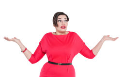 Beautiful plus size woman in red dress shrugs her shoulders Royalty Free Stock Image