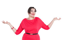 Beautiful plus size woman in red dress shrugs her shoulders Royalty Free Stock Photo