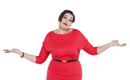Beautiful plus size woman in red dress shrugs her shoulders Stock Photography