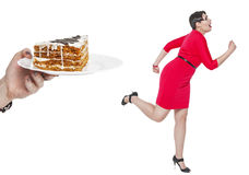 Beautiful plus size woman run away from cake isolated. On white background Royalty Free Stock Photo
