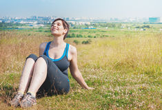 Beautiful plus size woman sitting on the meadow outdoor Stock Photo