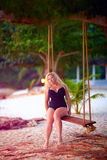Beautiful plus size woman sitting on tree swings, summer vacatio Royalty Free Stock Image