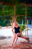 Beautiful plus size woman sitting on tree swings, summer vacation. Beautiful plus size woman sitting on tree swings, summer tropical vacation stock image