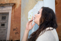 Beautiful plus size woman smokes  cigarette. Against an old building Stock Image