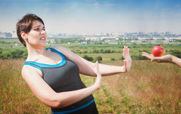 Beautiful plus size woman in sportswear refusing healthy food Royalty Free Stock Images