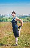 Beautiful plus size woman stretching outdoor Royalty Free Stock Photography